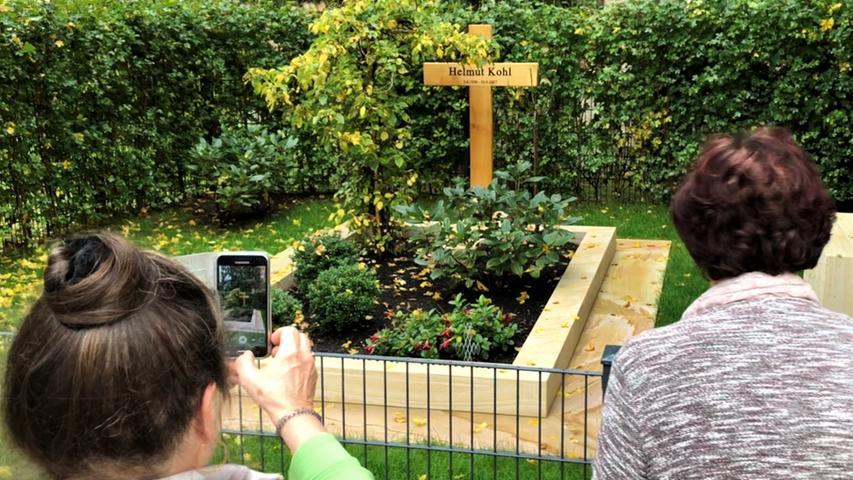 """Besucher sind an den Kanzlergräbern von Ohlsdorf bis Gmund am Tegernsee nur höchst selten anzutreffen. Bei Kohl schauen immerhin an einem regnerischen Nachmittag gleich drei Touristen vorbei. """"Da isser ja"""", rufen sie aus, als sie das Grab entdeckt haben, und holen nach kurzem pietätvollem Innenhalten ihre Smartphones aus der Tasche. Für Erinnerungsfotos."""