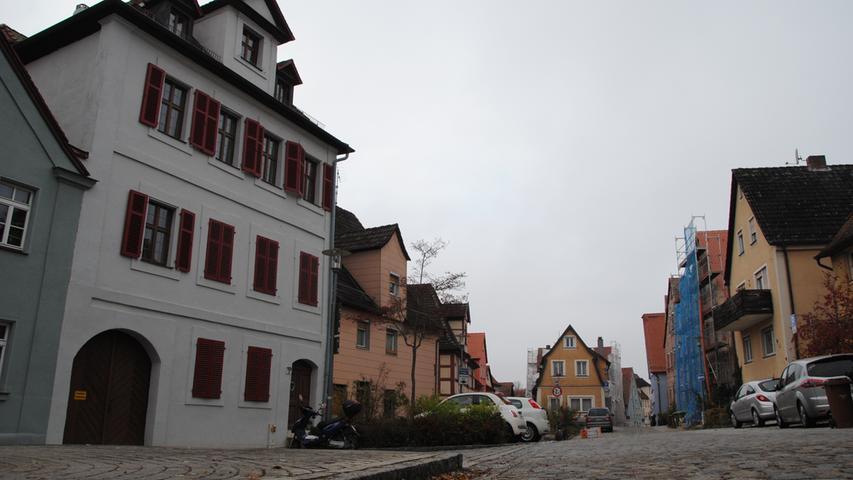Am Pinzenberg ist zuletzt das große Gebäude links neu gestrichen worden, im Hintergrund sieht man ein eingerüstetes Haus, wo der neue Anstrich noch bevorsteht.