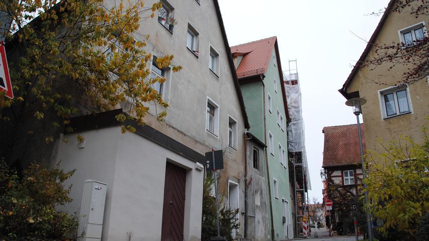 Dasselbe Gebäude von der anderen Seite, in der Schulgasse. Ein typischer Anblick für die nördliche Altstadt: Links ein heruntergekommenes Haus, mittig das sanierte Haus, rechts davon ein in Arbeit befindliches Haus. Und auf der anderen Seite: Schwabacher Fachwerk.
