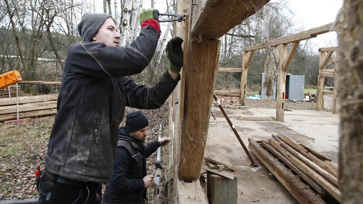 Sascha Troßmann und Sebastian Pfister von der Zimmerei Lederer aus Flachslanden tragen Balken für Balken der 320 Jahre alten Scheune ab.