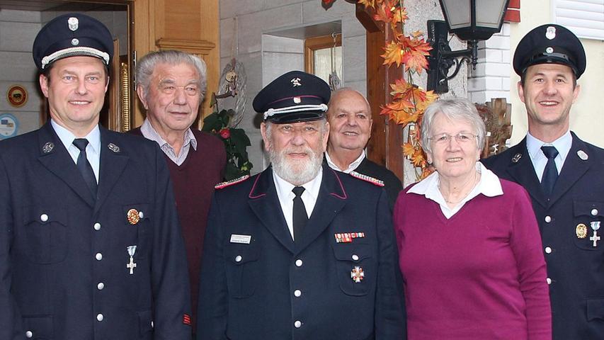 """Der Elmshorner Wolfgang Hergesell (M.) ist für 30-jährige Treue zur Feuerwehr Krottensee geehrt worden. 1987 verbrachte er das erste Mal mit Frau Elisabeth (2.v.re.) – ebenfalls seit über 25 Jahren Mitglied – einen Urlaub im Neuhauser Ortsteil. 1989 trat er der Feuerwehr bei, die in diesem Jahr ihr 100-jähriges Jubiläum feierte. Dieser """"tollen Truppe"""" ist der Jubilar, der immer wieder Urlaubstage im Ort verbringt, bis heute treu geblieben und unterstützt sie immer wieder finanziell. Die beiden Vorsitzenden Martin Lauß (l.) und Christian Schreg (r.) nutzten den Urlaub, um Wolfgang Hergesell zu ehren. Ehrenkommandant Hermann Lauß (hinten r.) und Ehrenvorsitzender Hans Wittmann (hinten l.) waren auch gekommen."""