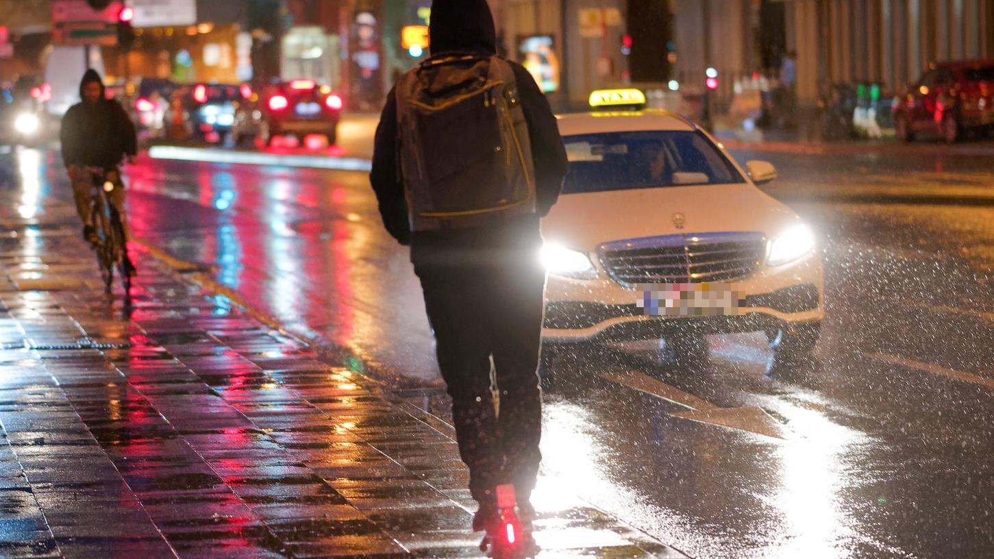 Ein E-Scooter fährt bei Regenwetter durch die Stadt. Bei schlechter Witterung müssen Fahrer einige Dinge beachten.
