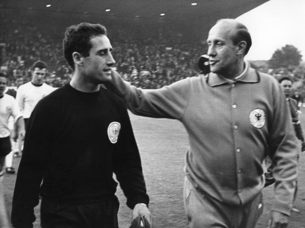 ARCHIV- Bundestrainer Helmut Schön (r) gratuliert am 12.7.1966 beim Verlassen des Rasens des Sheffielder Hillsborough-Stadions seinen Torhüter Hans Tilkowski (l). Foto: dpa (zu dpa: