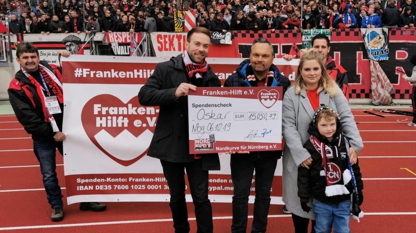 Club-Fans hatten auf ihr Becherpfand verzichtet. Im Max-Morlock-Stadion überreichten Andreas Brandl, Vorstandsmitglied des Vereins Franken-Hilft, und David Bartlitz (vorne links) den Spendenerlös an den kleinen Oskar und seine Mutter Janina.