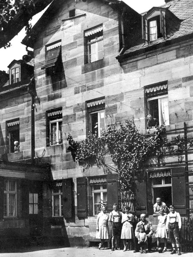 """""""Karls Geburtshaus"""" um das Jahr 1920: Im Hof vor dem Gebäude stellen sich die damaligen Bewohner zum Gruppenbild auf."""