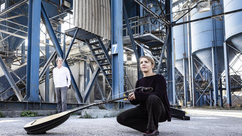 """Eine unwirkliche Kulisse für eine sehr sinnliche Angelgenheit: Johannes Reichert (links) und Christine Riessner mit ihrer Theorbe im Nürnberger Hafengelände. Bilder wie diese zieren ihr neues Alblum """"No no I never was in love""""."""