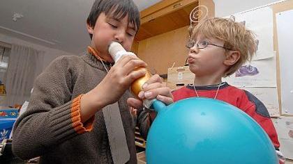 Marvin (li) hat aus einem Luftballon und Papprohr einen Dudelsack gebaut, mit dem er seinen Spielkameraden kräftig den Marsch blasen kann.