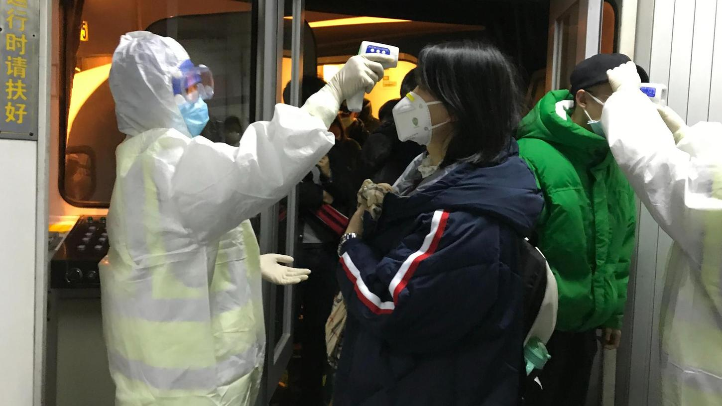 Gesundheitsbeamte in Chemikalienschutzanzügen kontrollieren am Flughafen von Peking die Körpertemperatur von Passagieren, die aus der Stadt Wuhan angereist sind. Dort sind bisher die meisten Fälle der neuartigen Lungenerkrankung aufgetreten.
