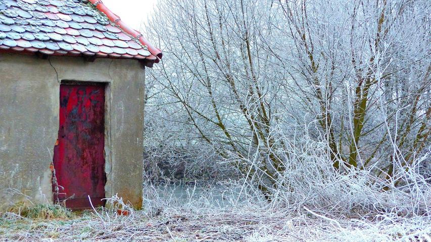 Bei dem alten Häuschen in Erlangen gibt die alte rote Tür einen idyllischen Kontrast zu der mit der Raureif überzogenen Umgebung.