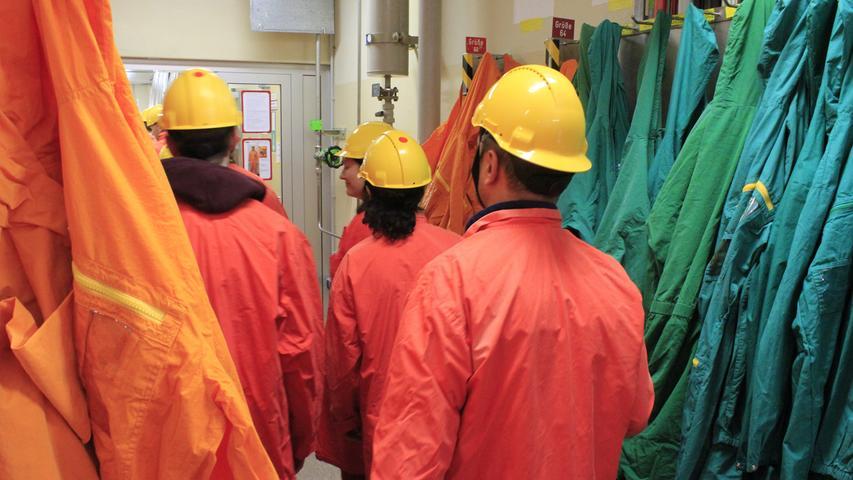 Wer das Kernkraftwerk in Grafenrheinfeld betreten will, muss Schutzkleidung tragen. Die Arbeiter stecken in orangefarbenen Kitteln, der Strahlenschutz in grünen. Besuchergruppen bekommen rote Mäntel und Überschuhe. In der Brusttasche misst ein Dosimeter die Strahlenbelastung während des Besuchs.