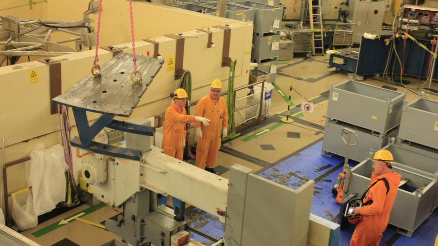 Arbeiter zerkleinern im Reaktorgebäude Bauteile so, dass sie in die bereitstehenden grauen Kisten passen.