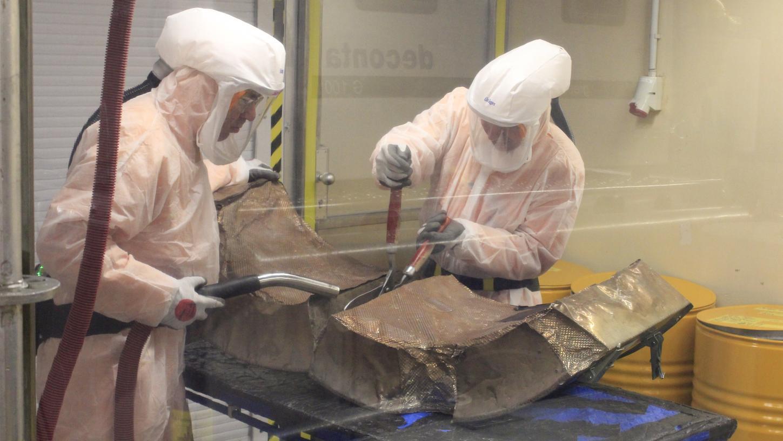 Diese beiden Arbeiter zerkleinern hinter einer Schutzscheibe die dicke Isolierung, die zuvor heiße Bauteile ummantelt hat. 130 Tonnen Isolierung wurden in den Jahren 2018 und 2019 bereits entfernt.