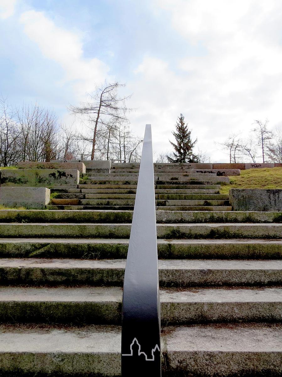 Im Volkspark Marienberg gibt es eine Treppe mit Aussicht auf Aussicht: Von oben hat man eine gute Sicht über Nürnberg auf die Kaiserburg in der Ferne. Das Piktogramm auf dem Geländer macht darauf aufmerksam und weist den Weg.
