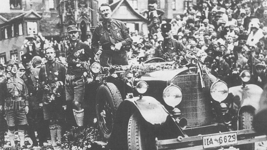 Reichsparteitag 1927 in Nürnberg: Parteivorsitzender Adolf Hitler steht in dem mit Blumen übersäten Wagen am Hauptmarkt. Neben ihm auf dem Trittbrett Franz Pfeffer von Salomon, Offizier zeitweise oberster SA-Führer. Er forderte schon 1925 unverblümt, behinderte Menschen, Waisen und Fürsorgezöglinge zu töten.
