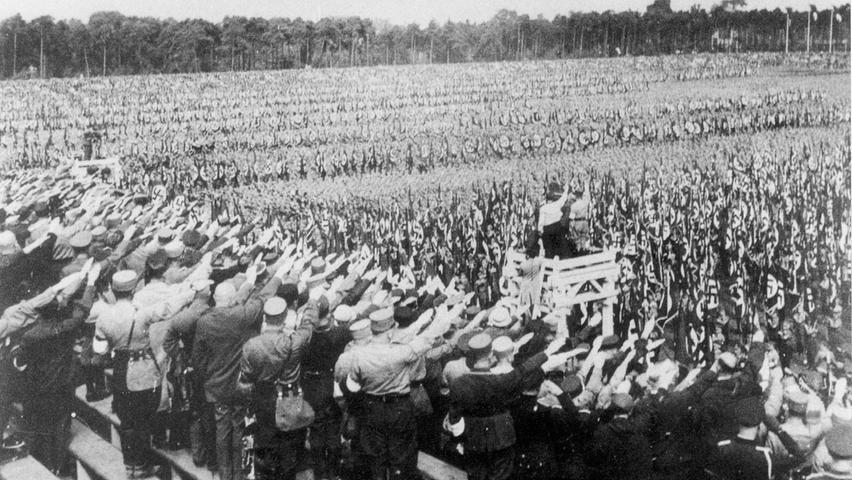 Dieses private Foto von 1933, entstanden auf dem Zeppelinfeld, zeigt deutlich die Massensuggestion der NS-Propaganda. Tausende Teilnehmer des Reichsparteitages recken die rechte Hand zum Hitlergruß.