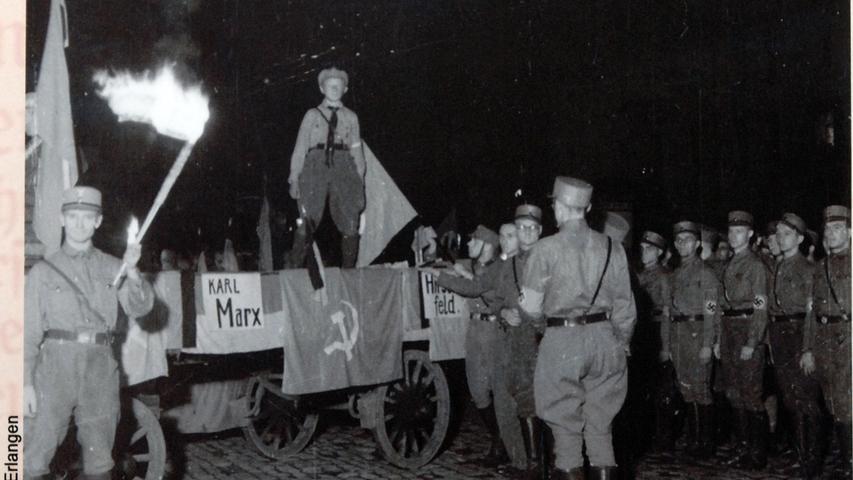 Am 12. Mai 1933 trafen sich Studenten auf dem Schlossplatz in Erlangen, um die Bücherverbrennung im Rahmen der 'Aktion wider den undeutschen Geist' durchzuführen.