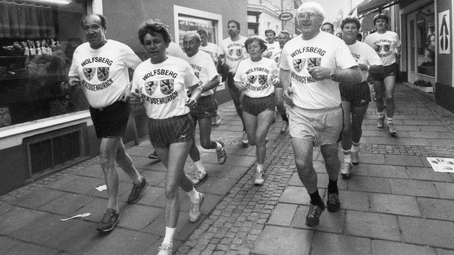 """Legendäres Ereignis in der langen Geschichte der Turnerschaft 1861: der Lauf nach Wolfsberg. Hier laufen Adam Hildel (links) und zahlreiche andere """"VIPs"""" aus Herzogenaurach ins Zentrum der Partnerstadt ein. Vorne rechts etwa Bürgermeister Hans Ort, 5. von links der mehrfache Senioren-Weltmeister Willi Scheidt."""
