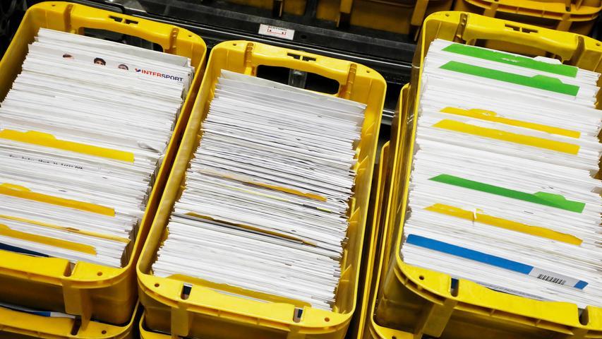 Die Post kommt vorsortiert in gelben Boxen an. Sie läuft im Briefzentrum durch die Maschine, die mit ihrer Software die Briefe in der Reihenfolge anordnet, wie der Postbote sie später austrägt.