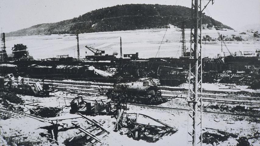 Auf fast jedem Gleis des Treuchtlinger Bahnhofs treffen die US-Bomber am 23. Februar 1945 Güter- und Personenzüge. Das Bild zeigt die Zerstörungen unweit des Bahnbetriebswerks mit dem Nagelberg im Hintergrund.