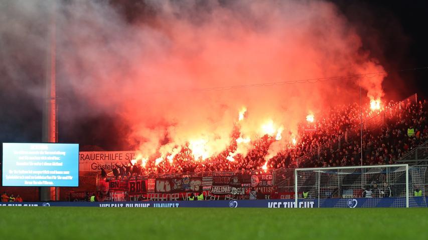 Das Spiel eröffnen die Karlsruher Fans mit einer Pyrotechnik-Einlage, die Clubfans auf der anderen Seite lassen ebenfalls nicht lange auf sich warten. Eine Minute nach dem Anpfiff ist der Rauch aber schon größtenteils wieder verzogen.