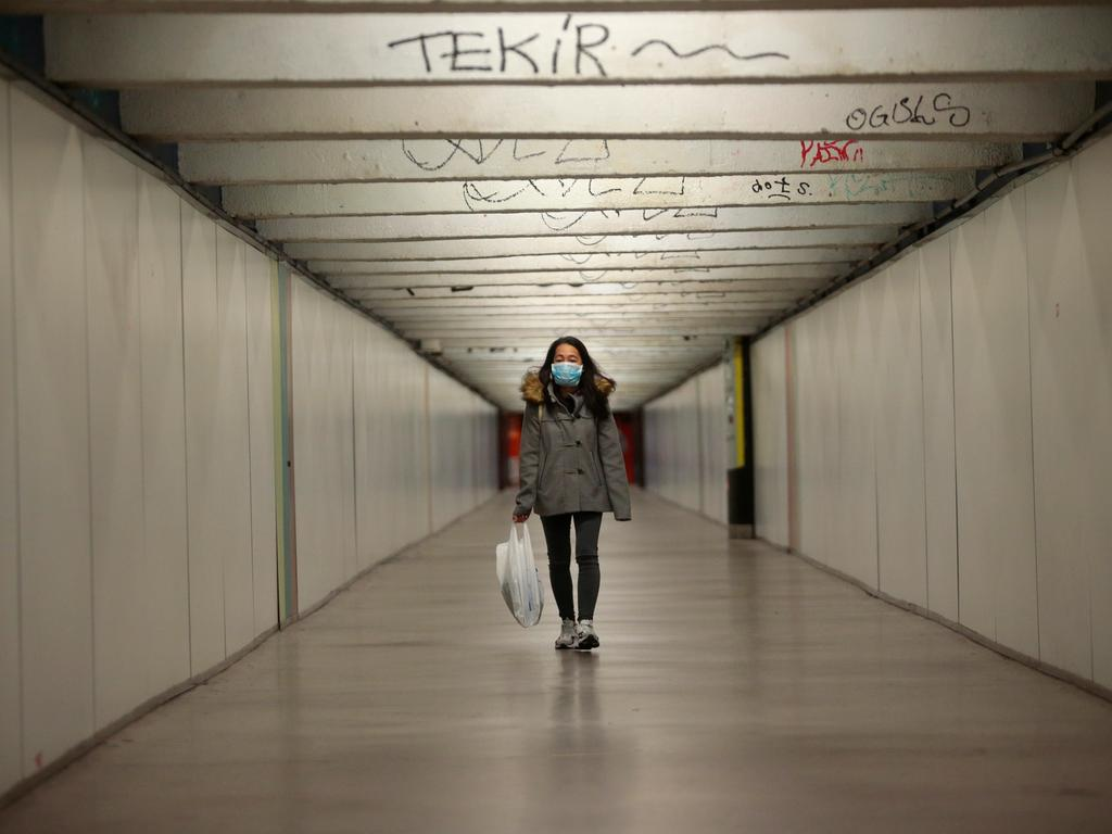 16.03.2020, Spanien, Barcelona: Eine Frau mit Mundschutz geht auf einem Bahnhof in Barcelona einen Durchgang entlang. Zur wirksameren Bekämpfung des Coronavirus hat Spanien einen zweiwöchigen sogenannten Alarmzustand verhängt, der auf die Einschränkung der Bewegungsfreiheit im ganzen Land hinausläuft. Foto: Joan Mateu/AP/dpa +++ dpa-Bildfunk +++