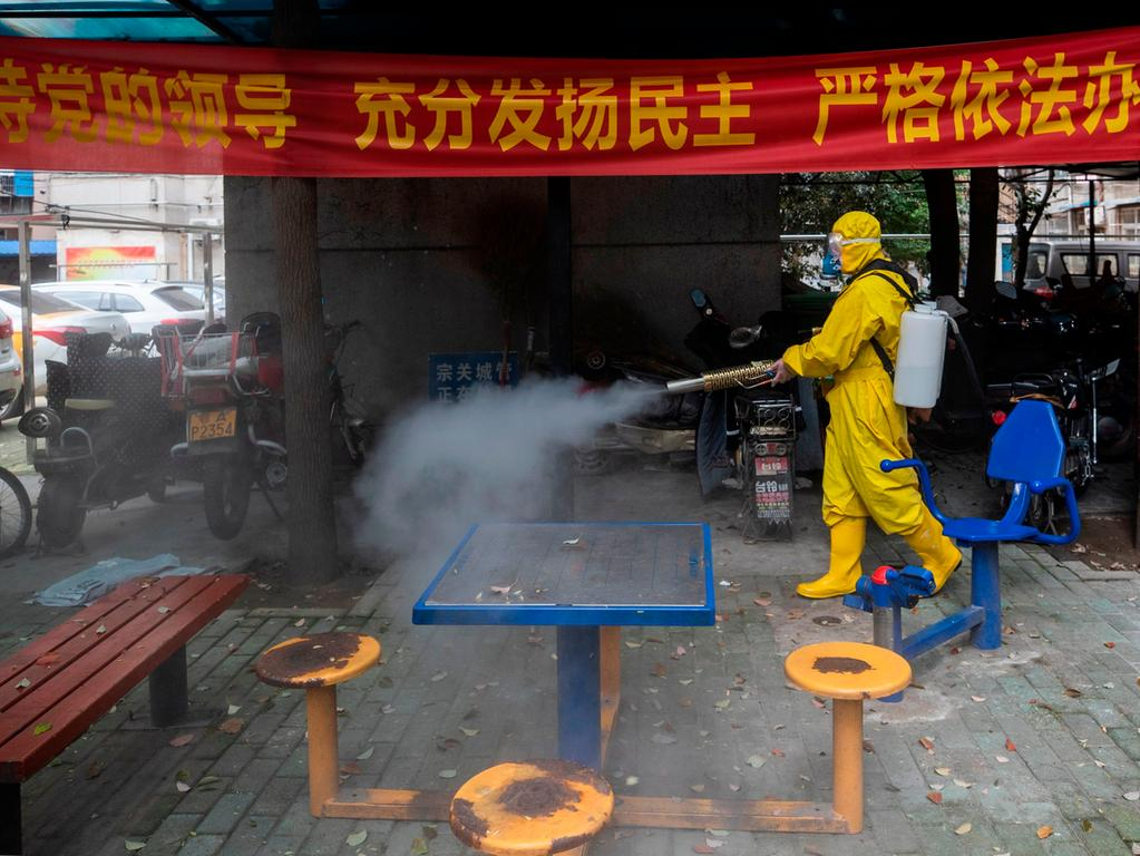 A volunteer disinfects a residental area amid the COVID-19 coronavirus outbreak in Wuhan in China's central Hubei province on March 16, 2020. - China tightened quarantine measures for international arrivals on March 16 as the country worries about a rise in imported cases of the deadly coronavirus and anger rages online at how Europe and the United States are handling the pandemic. (Photo by STR / AFP) / China OUT