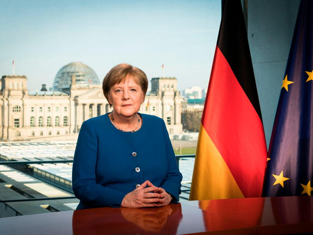 This Handout photo made available by the German Press Office shows German Chancellor Angela Merkel posing for a photo at the recording of a TV address to the nation on the spread of the new coronavirus COVID-19 at the Chancellery, with a view of the Reichstag, the building housing the lower house of parliament, through the window in Berlin on March 18, 2020. (Photo by Steffen Kugler / Bundesregierung / AFP) / RESTRICTED TO EDITORIAL USE - MANDATORY CREDIT