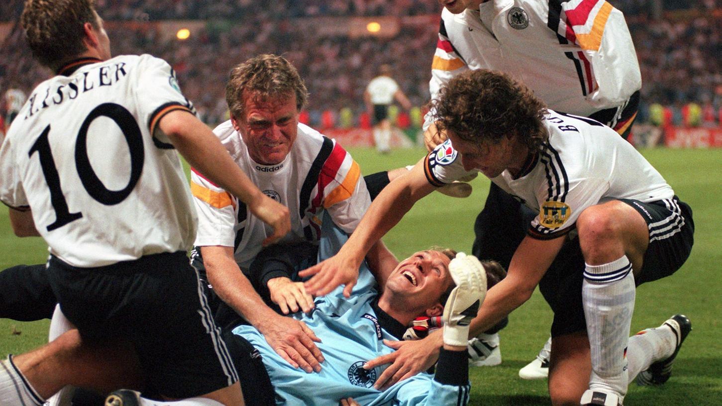 Von seinen Mannschaftskameraden Thomas Häßler (l), Marko Bode (r), Fredi Bobic (dahinter) und Torwart-Trainer Sepp Maier (2.v.l.) umjubelt, liegt der deutsche Torwart Andreas Köpke nach dem 6:5-Sieg im Elfmeterschießen beim Halbfinalspiel der Fußball-Europameisterschaft EURO '96 zwischen Deutschland und England auf dem Rasen des Londoner Wembley-Stadions.