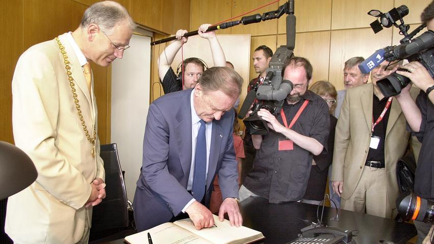 Umringt von den Kameras trägt sich Albert Uderzo ins Goldene Buch der Stadt Erlangen ein. OB Siegfried Balleis schaut sichtbar glücklich zu.