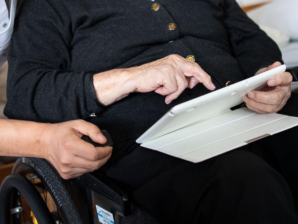 ARCHIV - 12.09.2018, Nordrhein-Westfalen, Neuss: Ein Altenpfleger schaut in der Seniorenresidenz mit der Bewohnerin ein Video an. (zu dpa «Hilfe per WhatsApp - Beratungsstellen ergänzen ihre Angebote») Foto: Marius Becker/dpa +++ dpa-Bildfunk +++