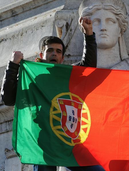 Die Demonstranten halten Fahnen und Plakate in die Höhe.