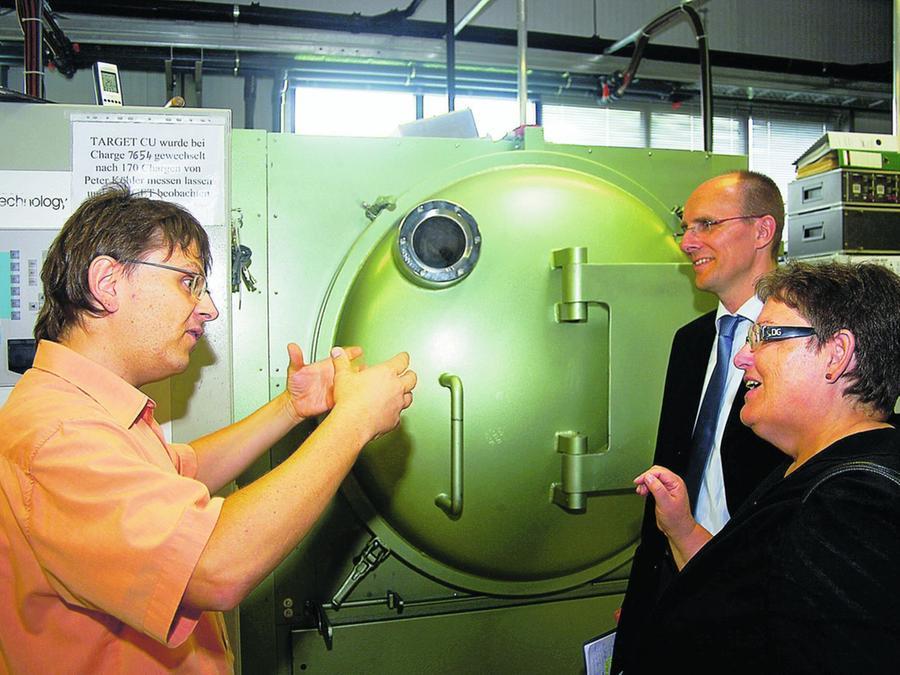 Firmenchef Christian Wohlrab erklärt SPD-Kreisvorsitzendem Michael Bischoff und SPD-MdB Marlene Rupprecht, wie eine Vakuumbeschichtung (grünes Gerät im Hintergrund) funktioniert.