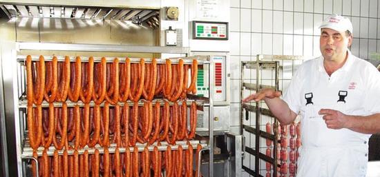 Metzger Rebelein aus Gunzenhausen erklärt seinen Gästen, wie er Räucherwürste produziert.
