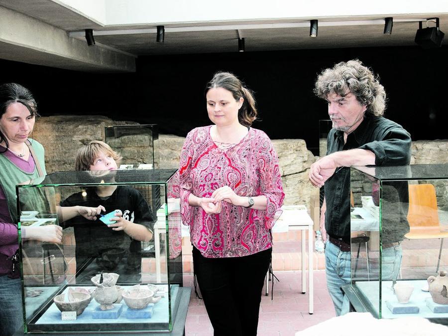 Die Archäologin (Bildmitte) erläutert einer interessierten Familie einige der unter dem Marktplatz ausgestellten Funde.