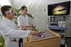Die Holzkiste simuliert die menschliche Bauchhöhle, aus der die Kamera Bilder aufs TV-Gerät überträgt — und das in 3D. Chefarzt Dr. Andreas Blana (links) und Dr. Ingo Warbruck sind von der neuen Technik begeistert.