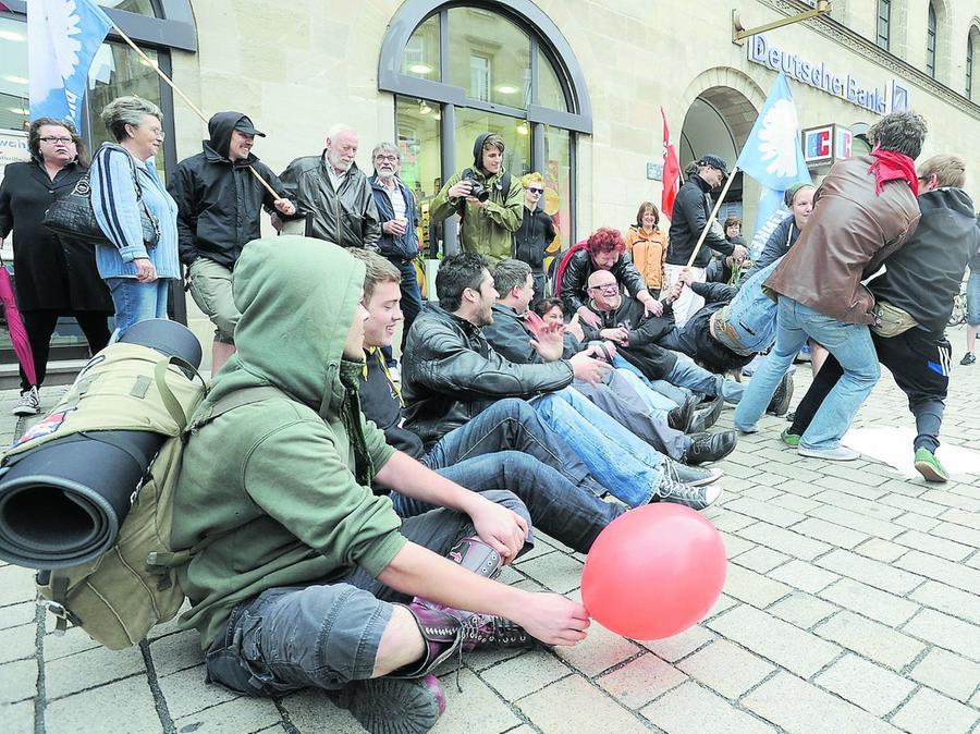 Zum Sitzblockade-Training haben sich Demonstranten am Occupy-Aktionstag vor der Deutschen Bank in der Fürther Fußgängerzone niedergelassen.