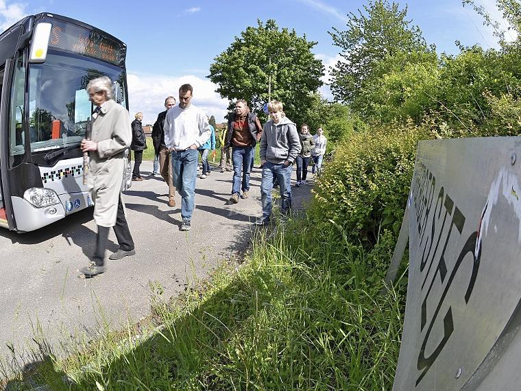 Tiefbauamtschef Hans Pösl (li.) und infra-Verkehrsbetriebsleiter Klaus Dieregsweiler (4. v. re.) demonstrieren Bürgern mit einem Linienbus die fehlende Wendemöglichkeit am Fürberger Steg.