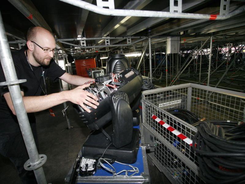 Während über ihm die Bässe wummern, überprüft Lichttechniker Frederik Leiße direkt unter der Centerstage die Scheinwerfer.