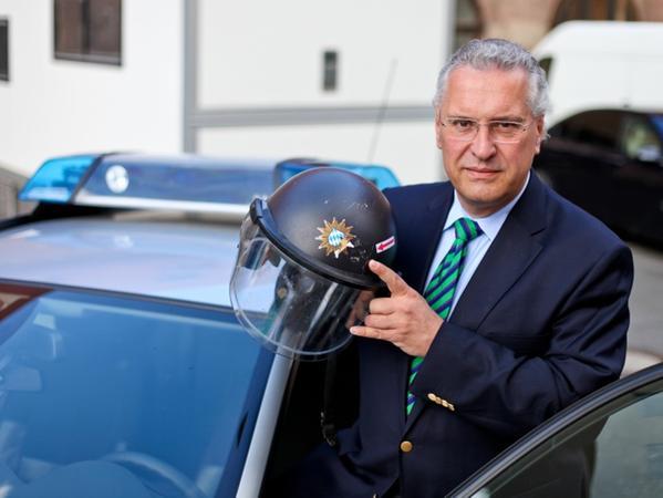 Innenminister Joachim Herrmann zeigt einen Polizeihelm, der durch massive Gewalteinwirkung beschädigt wurde.
