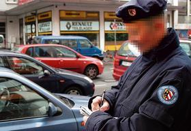 Ein Mitarbeiter der kommunalen Verkehrsüberwachung stellt einen Strafzettel aus.