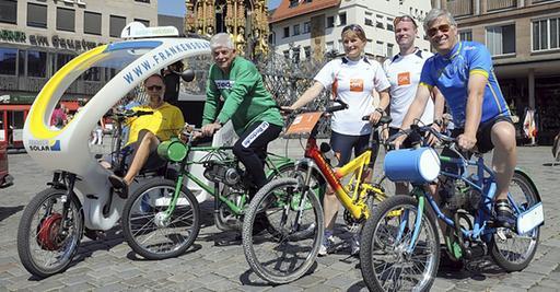 Fototermin am Schönen Brunnen: Fahrrad-Taxis, Derny-Rennen und ein neuer Bike-and-Rund-Wettbewerb werden symbolisch  präsentiert. Nur echte Rennräder fehlen auf dem Bild, aber auch die wird es am 12. September geben.