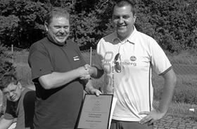 Während der Busfahrt zum Bundesliga-Auswärtsspiel des 1. FC Nürnberg bei der SG Eintracht Frankfurt wurde der 1. FCN-Fanclub Wiesenthau von der Deutschen Olympischen Gesellschaft (DOG) zum 25-jährigen Jubiläum geehrt. Natürlich wurde der Jahrestag gefeiert. Andreas Dippold (links), Vorstandsmitglied und Kassier des 1. FCN-Fanclubs Wiesenthau bekam von Andreas M. Tschorn (rechts), Vorstandsvorsitzender der Bezirksgruppe Oberfranken-Süd der Deutschen Olympischen Gesellschaft die DOG-Ehrenurkunde überreicht. Zwar reichte es für den Club dann nur zum Unentschieden, doch die Ehrenurkunde tröstete über den verpassten Sieg hinweg.
