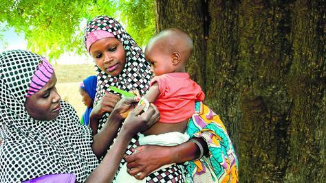 Die beiden Helferinnen Lantana und Garba gehen von Haus zu Haus, um gegen Fehl- oder Unterernährung vorzugehen. Mit einer Schablone vermessen sie die Armdicke bei den Kleinen.