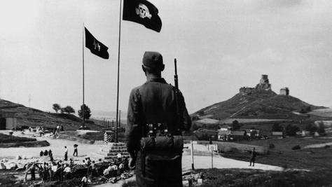 Während die Zwangsarbeiter im Steinbruch Burgberg unter schlimmsten Bedingungen schuften mussten, bewacht ein wärter der SS-Totenkopfbrigade die Menschen.