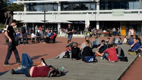 Studenten sonnen sich auf dem Roten Platz vor der TechFak in Erlangen.