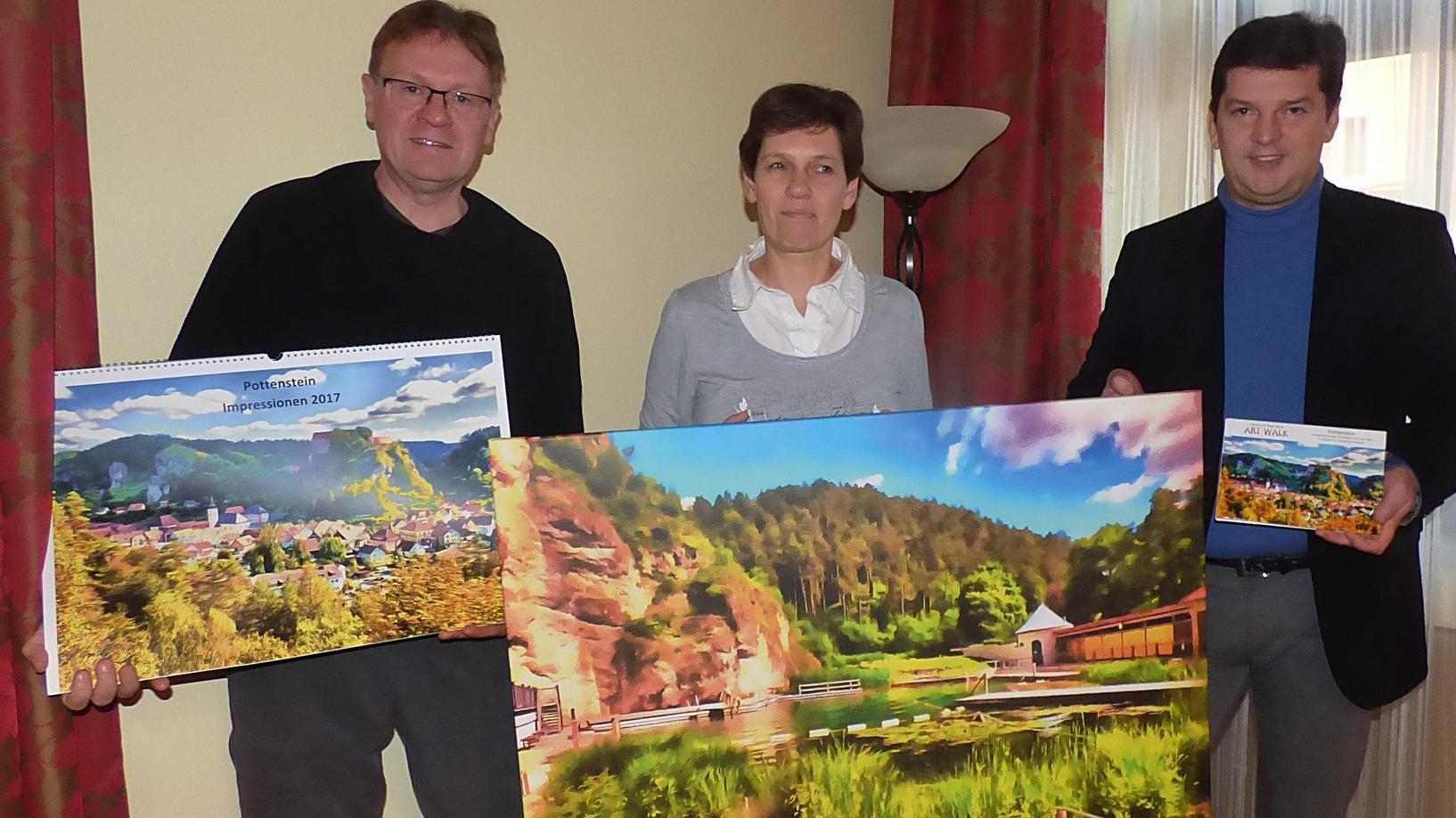 Bürgermeister Stefan Frübeißer (rechts) und das Berliner Künstlerpaar Marina und Ralph Kähne zeigen einige ihrer Ansichten von Pottenstein. Diese reichen vom Kleinformat über Kalender bis zu einem großen Poster.