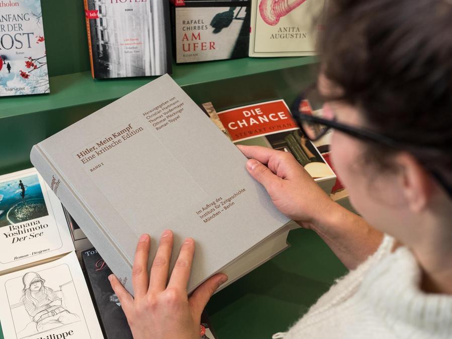 """Eine Buchhändlerin zeigt ein Exemplar der neuen, kritischen Ausgabe von Hitlers """"Mein Kampf""""."""