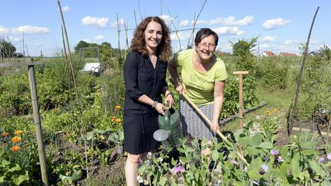 Garten-Vorsitzende Monika Zacherl (rechts, hier mit einer Erlanger Politikerin) greift im Sommer fast täglich zu Harke und Gießkanne.