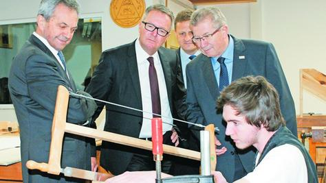 So wird die Säge für einen perfekten Schnitt angesetzt: Ein Zimmerer zeigt Landrat Gerhard Wägemann, Schulleiter Thomas Grad, HWK-Präsident Thomas Pirner und Landratsvize Robert Westphal (von rechts), wie es geht.