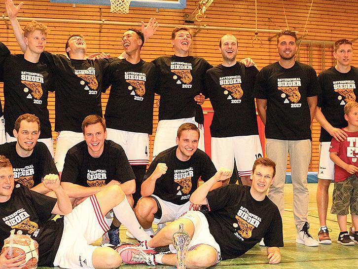 """Turbulentes Finale: Nach einem spannenden und umkämpften Spiel gegen TTL Bamberg durfte das Team des VfL Treuchtlingen, das diesmal von Marius Lang (Zweiter von rechts) gecoacht wurde, den erstmaligen Gewinn des Bayernpokals feiern. Dementsprechend ausgelassen war die Stimmung nach dem """"i-Tüpfelchen"""" auf die bislang erfolgreichste Saison der heimischen Baskets."""